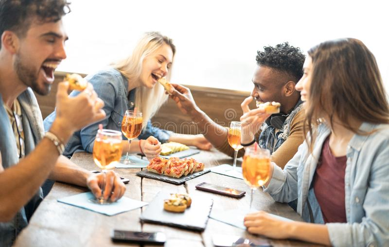 Friends eating and drinking spritz at fashion cocktail bar restaurant - Friendship concept with young people having fun together royalty free stock photography