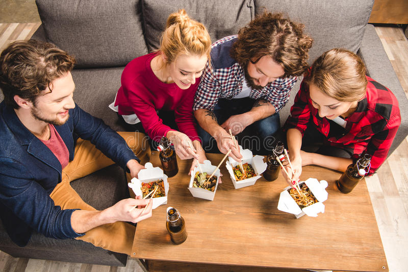 Friends eating noodles. Happy friends sitting on sofa and eating noodles with chopsticks stock photography