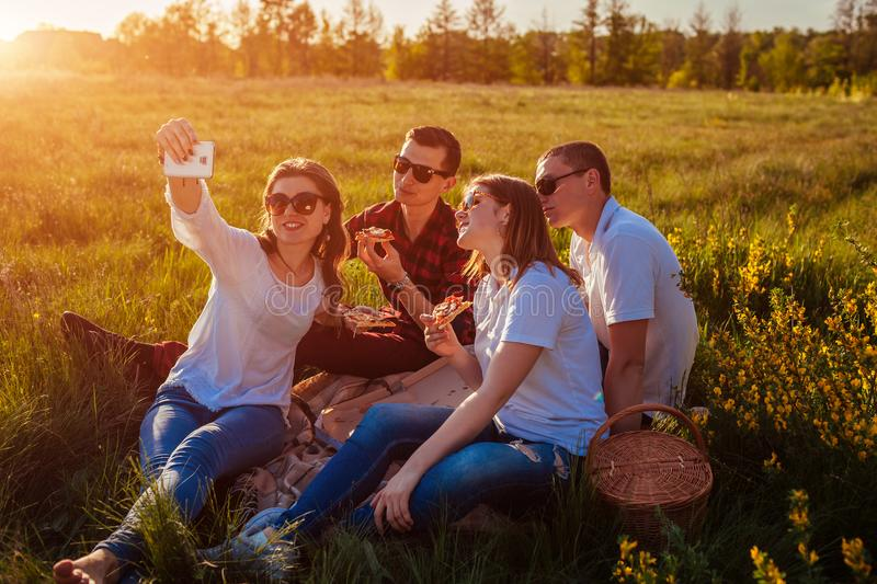 Friends eating pizza outside and taking selfie. Women and men having picnic at sunset. Fast food concept. stock image