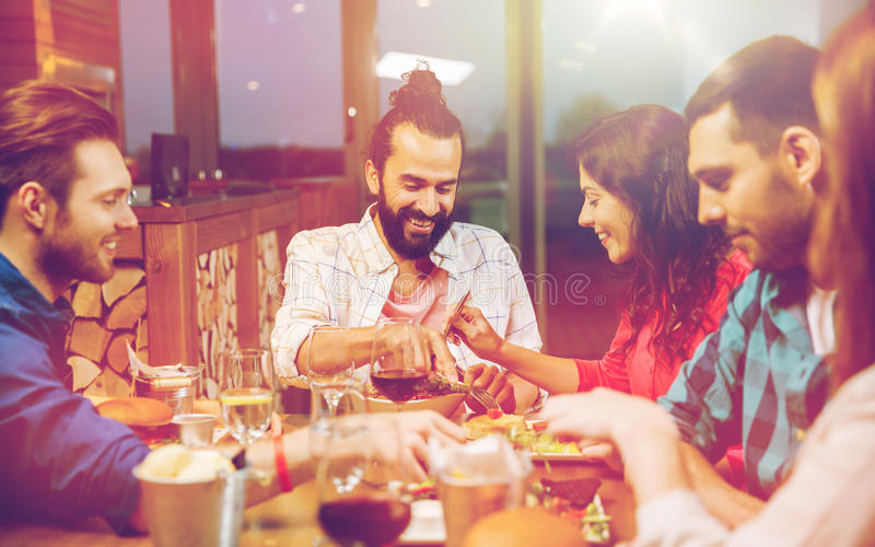 Friends eating and tasting food at restaurant. Leisure, eating, food, people and holidays concept - smiling friends having dinner and tasting each other dish at royalty free stock images