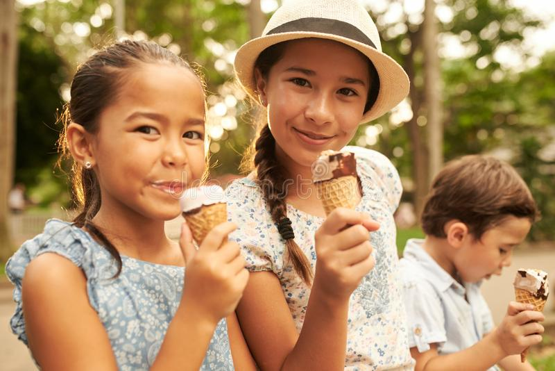 Cheerful children. Friends eating tasty ice-cream in waffle cones stock photography