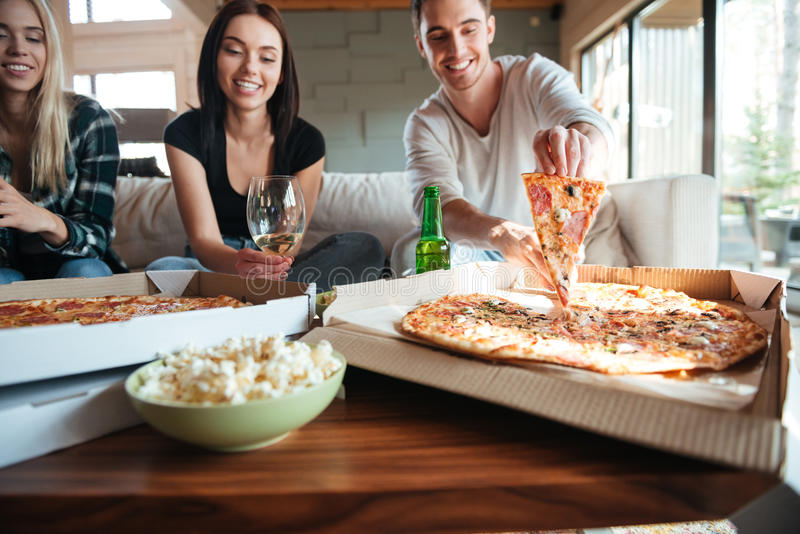 Friends eating tasty pizza at home while having a party stock images