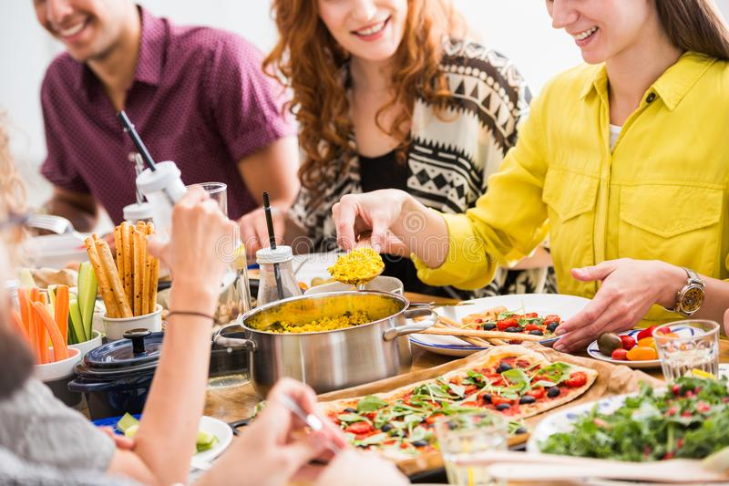 Friends eating vegetarian breakfast. Young women putting yellow tofu scramble on her plate, group of friends eating vegetarian breakfast together while sitting stock image
