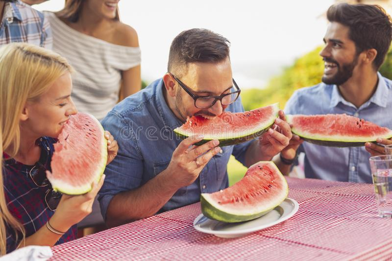 Friends eating watermelon. Group of friends having an outdoor lunch, eating fresh watermelon slices and having fun stock photo