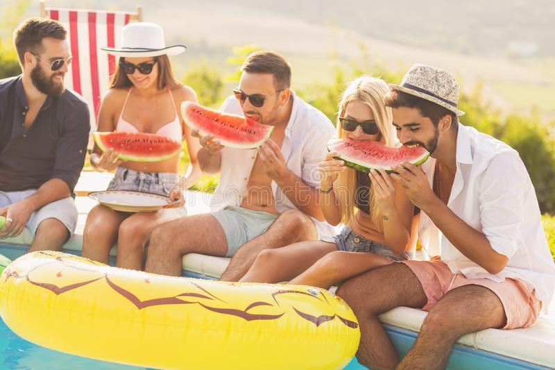 Friends eating watermelon. Group of friends at a poolside summer party, sitting at the edge of a swimming pool, eating cold watermelon slices and having fun stock photo