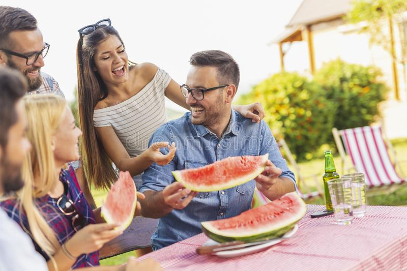 Friends eating watermelon at summertime party royalty free stock photo