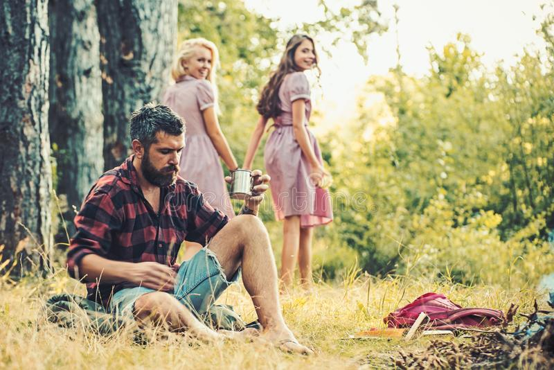 Friends enjoy camping in forest. Bearded man drink tea at bonfire with women on blurred background. Hipster with beard stock image