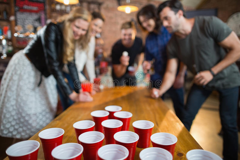 Friends enjoying beer pong game in bar stock image