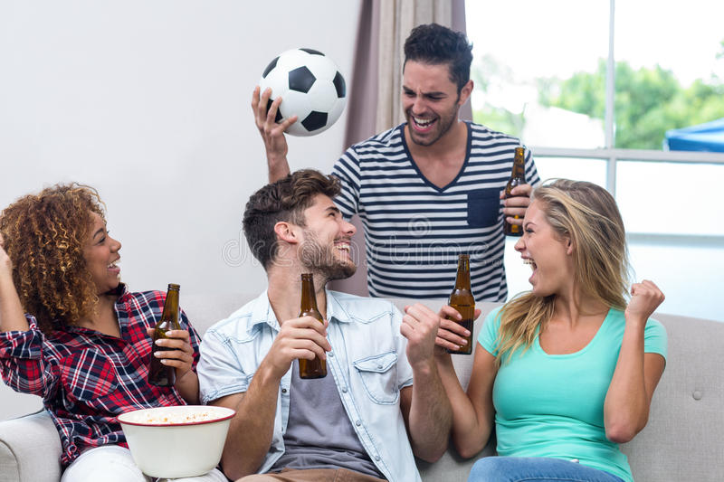Friends enjoying beer while watching soccer match stock images