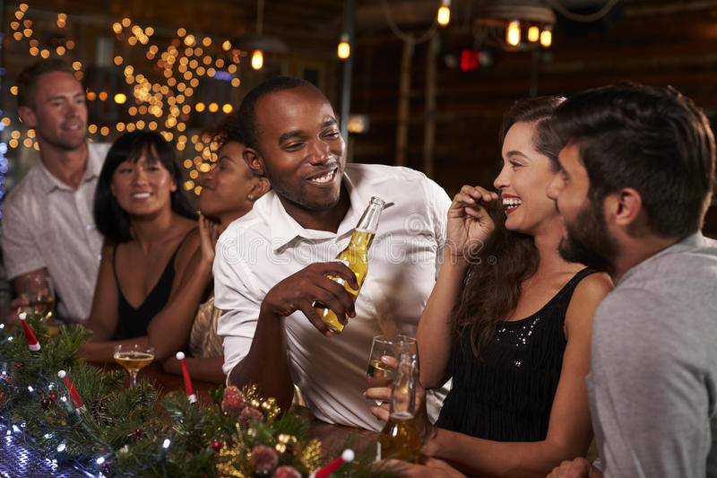 Friends enjoying a Christmas party talk at the bar stock photos