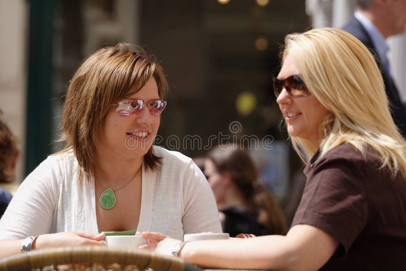 Friends enjoying coffee. Two young ladies having coffee in the sun stock photo