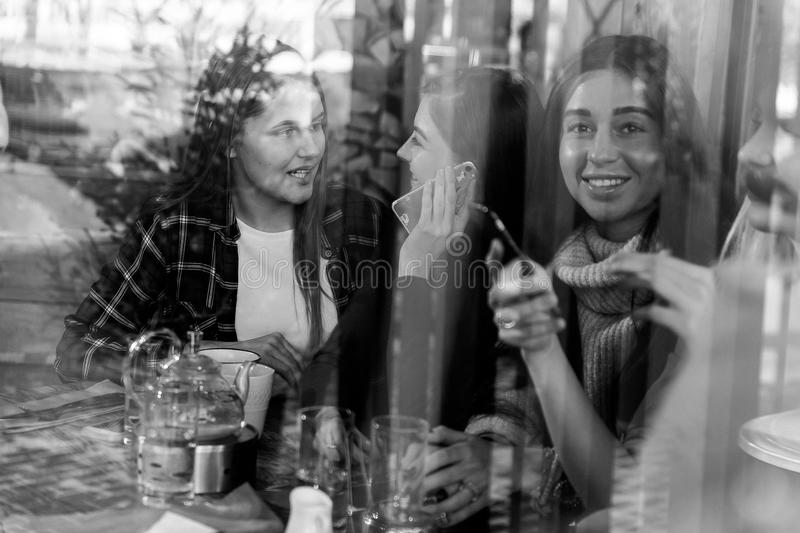 Friends enjoying coffee together in a coffee shop viewed through glass with reflections royalty free stock photo