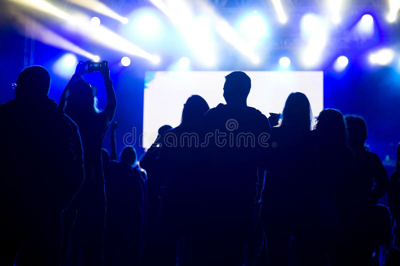 Friends enjoying concert, people dancing at a party. Silhouettes stock photography