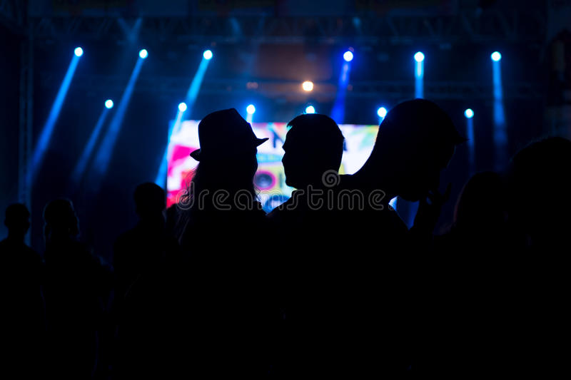 Friends enjoying concert, people dancing at a party. Silhouettes stock photos