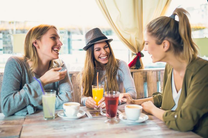 Friends enjoying in conversation and drinking coffee. stock photo