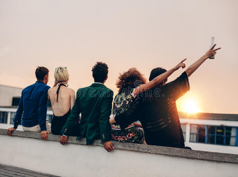 Friends enjoying drinks on rooftop at sunset. Group of friends partying on terrace with drinks. Young men and women enjoying drinks on rooftop at sunset royalty free stock images