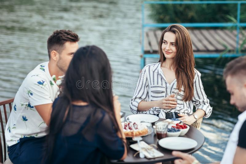 Friends enjoying meal during the dinner in outdoor restaurant stock images