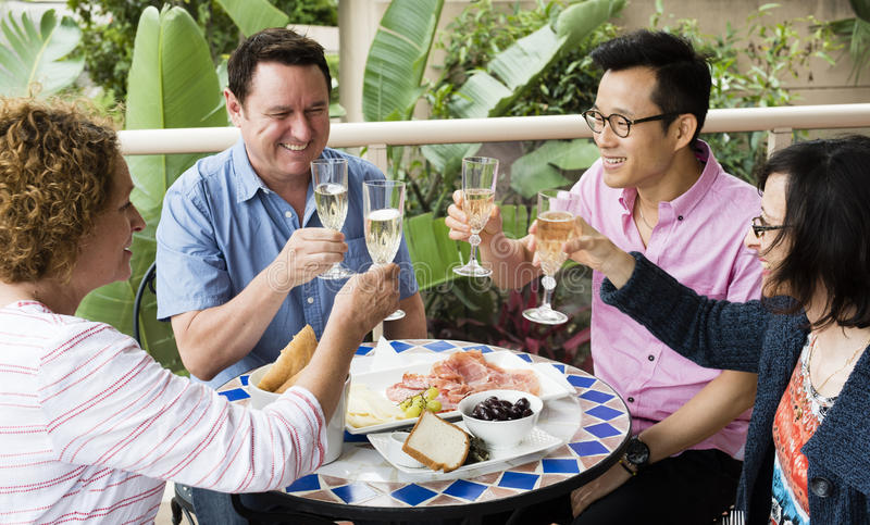 Friends enjoying a meal together. Friends proposing a toast during a Sunday lunch royalty free stock image