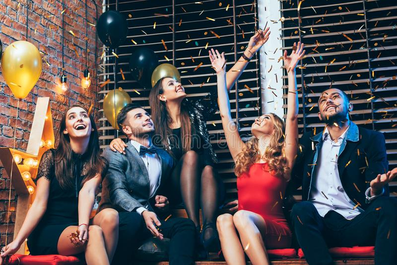 Friends enjoying party and having fun throwing confetti. royalty free stock photo