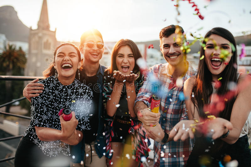 Friends enjoying party and throwing confetti stock photography