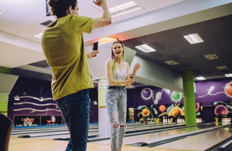 Friends enjoying playing at bowling arena royalty free stock photos
