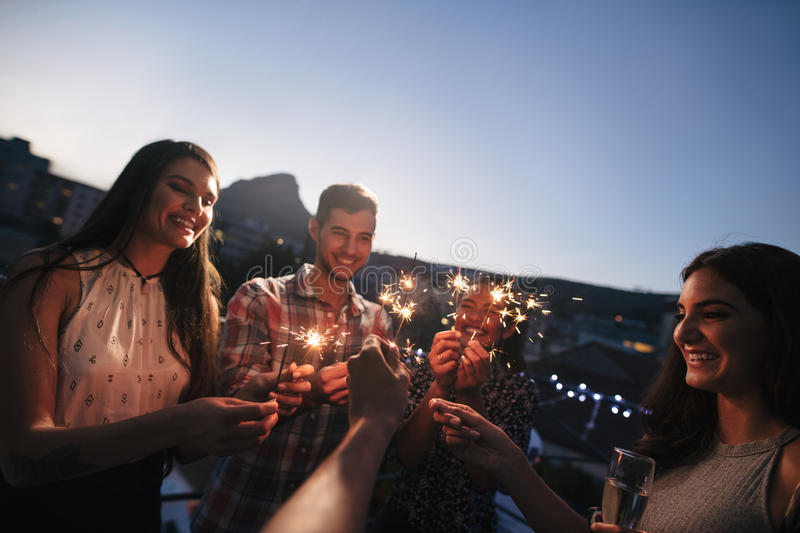 Friends enjoying rooftop party with sparklers stock image