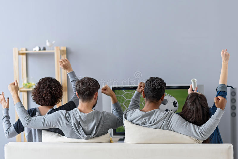 Friends enjoying soccer in TV stock photography