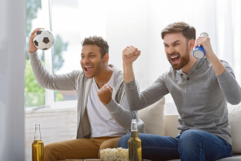 Friends enjoying soccer in TV. This is sport only for men. Cropped photo of two excited soccer fans watching tv at home with window in background stock photos