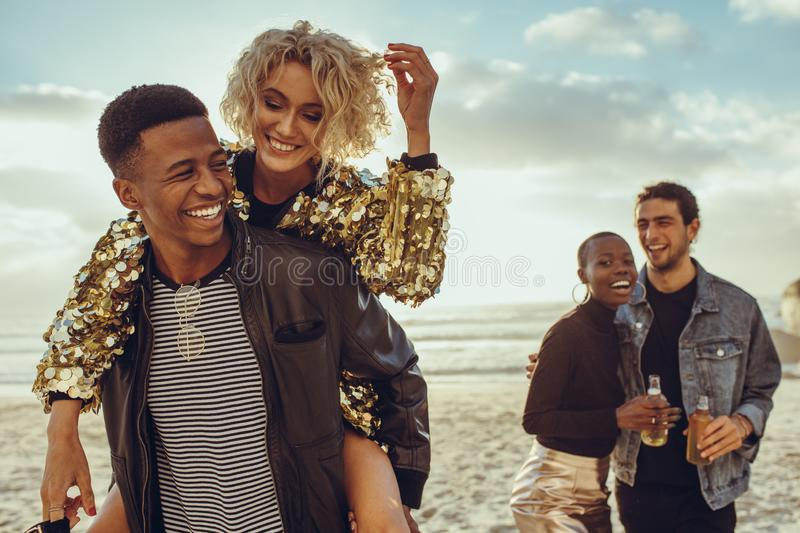Friends enjoying themselves on their beach holiday. Man piggybacking women with friends walking at the beach. Multiracial friends enjoying themselves on their royalty free stock image