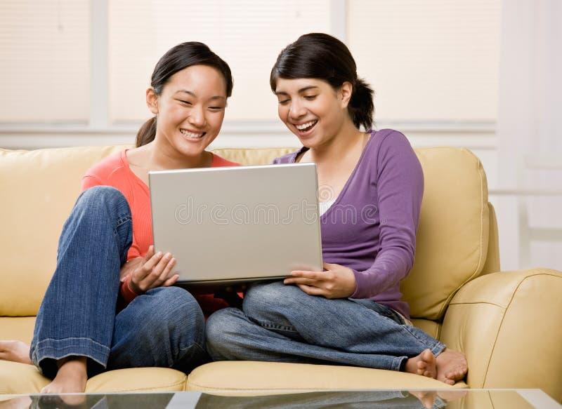 Friends enjoying using the laptop on sofa royalty free stock photo