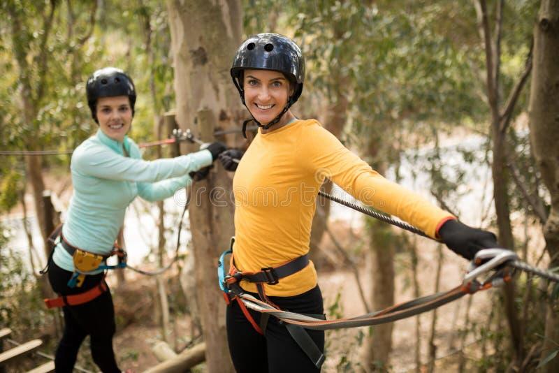 Friends enjoying zip line adventure in park stock photos