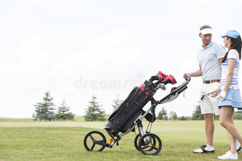 Friends with equipment talking while walking at golf course against clear sky stock images