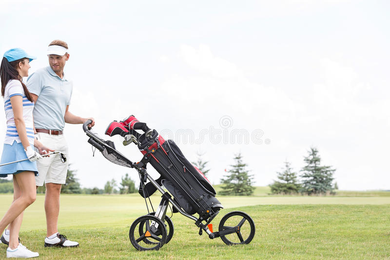Friends with equipment talking while walking at golf course against clear sky stock image