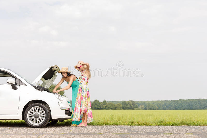 Friends examining broken down car on country road against clear sky stock photography