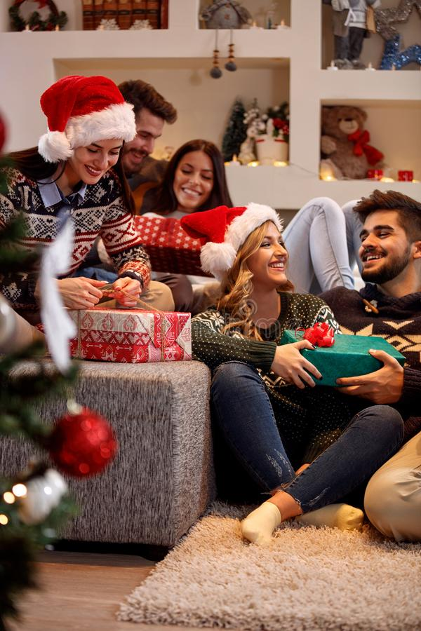 Friends exchanging gift boxes at Christmas eve royalty free stock photos