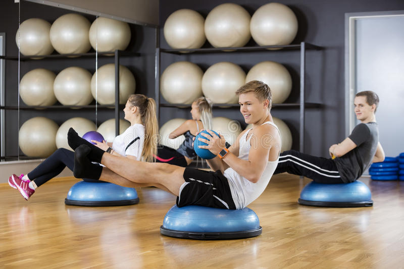 Friends Exercising With Medicine Ball In Gym royalty free stock photos