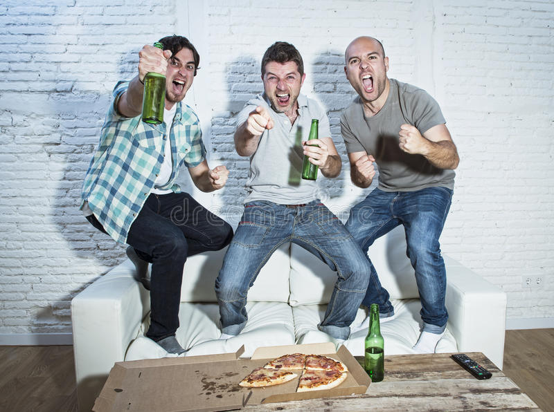 Friends fanatic football fans watching game on tv celebrating go royalty free stock photography