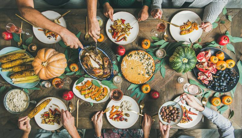 Friends feasting at Thanksgiving Day table with turkey and wine. Thanksgiving or Friendsgiving holiday celebration party. Flat-lay of friends feasting at stock images