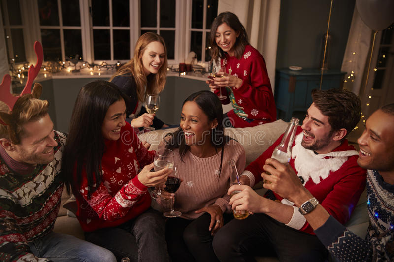 Friends In Festive Jumpers Celebrate At Christmas Party royalty free stock image