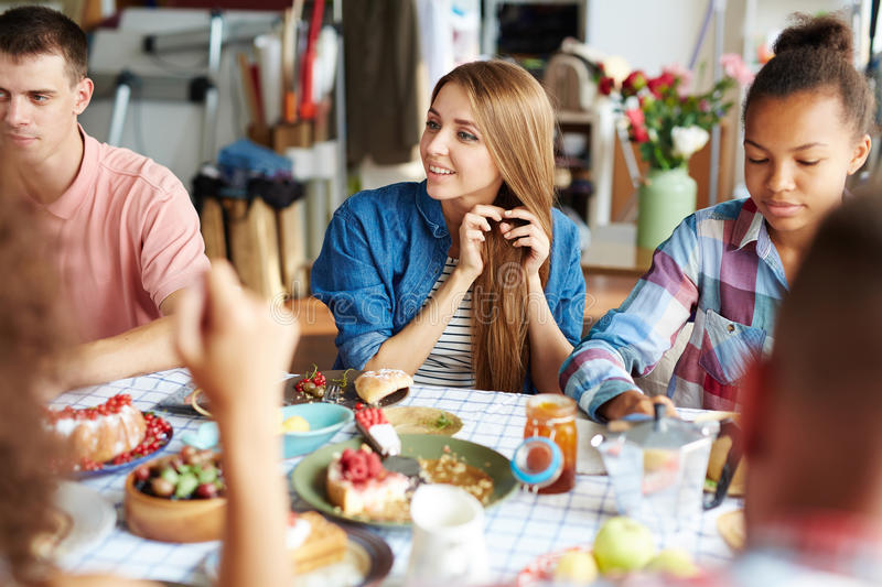 Friends by festive table stock photography