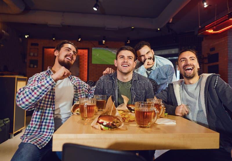Friends flans tittar på sporttv i puben arkivfoton