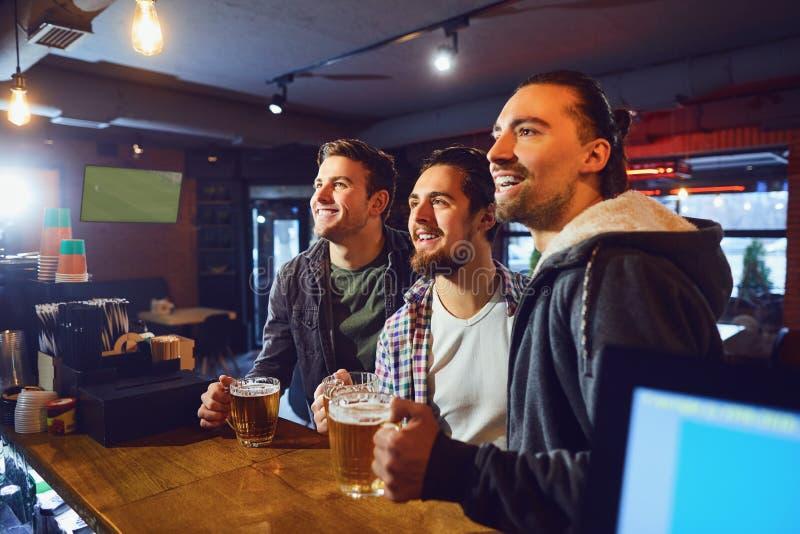 Friends flans tittar på sporttv i puben royaltyfri foto