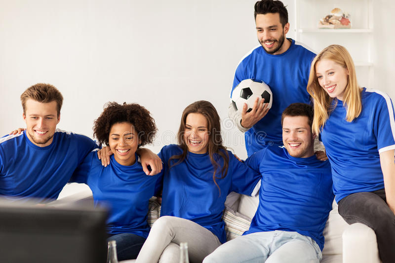 Friends or football fans watching soccer at home stock image