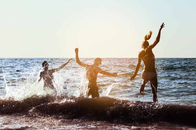 Friends fun party beach sunset group. Goup of three friends having fun or dancing at beach party at sunset time. Space for text stock image