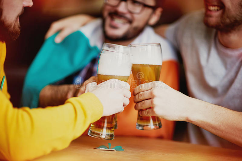 Friends Get Together for Craft Beer. Closeup shot of three men clinking classic tall glasses with foamy lager beer, enjoying their meeting at Irish Pub stock photography