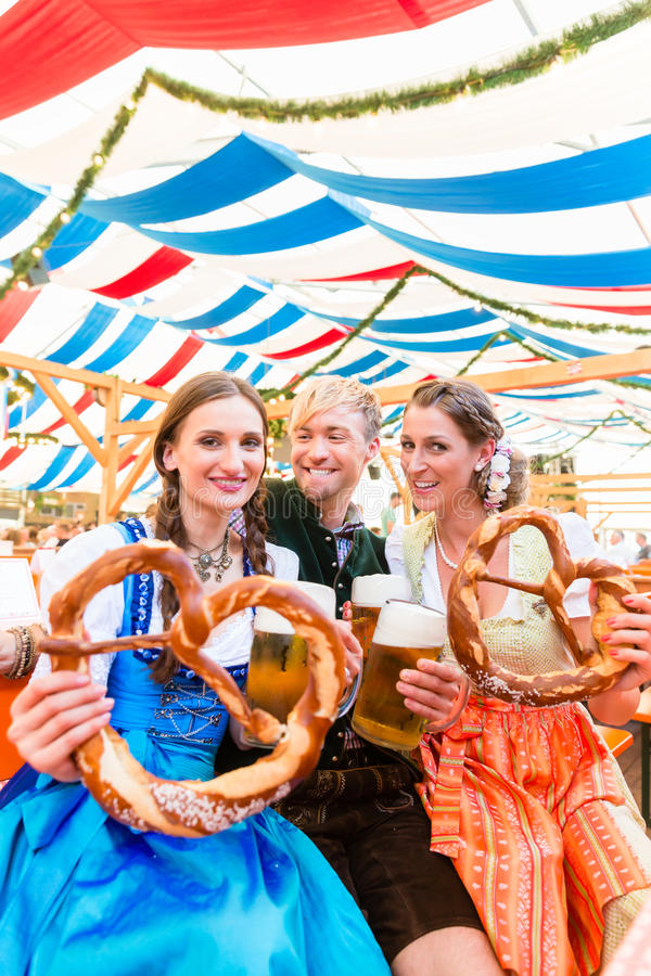 Friends with giant pretzels in Bavarian beer tent. Three friends in beer tent at Dult or Oktoberfest holding giant pretzels up in the air royalty free stock photos