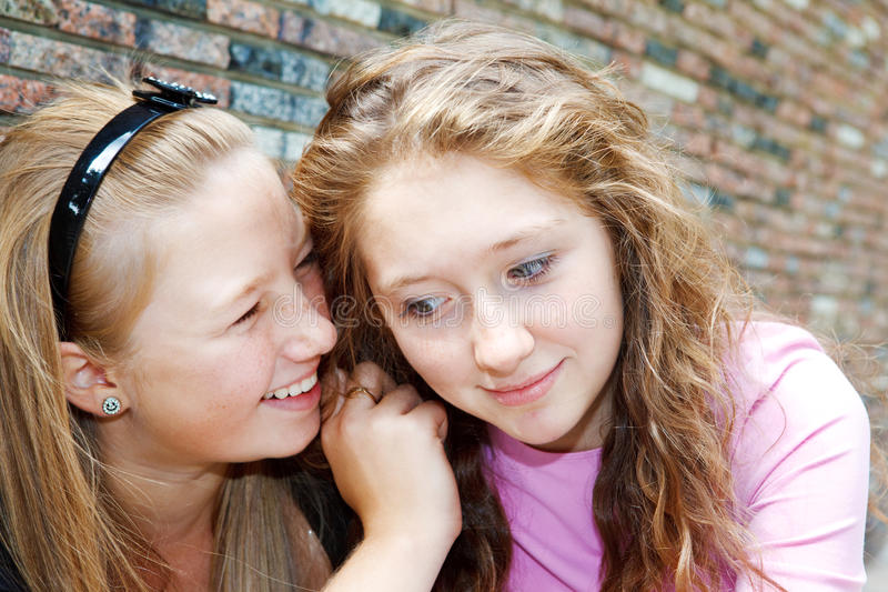 Friends gossiping. Two teenage female friends gossiping stock photography