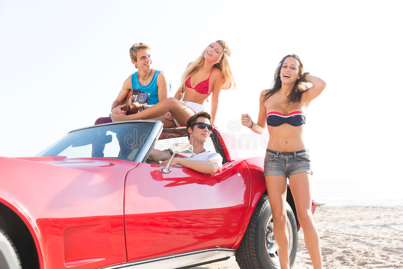 Friends group at beach in sports car convertible stock images