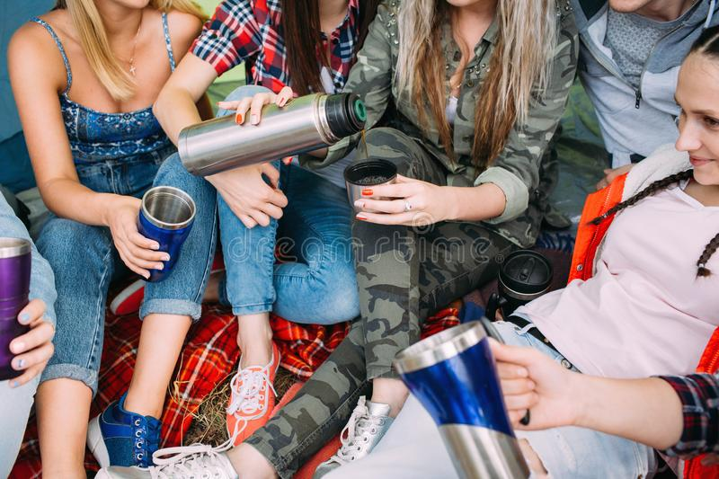 Friends group get warm with tea in the tent. Picnic time royalty free stock photo
