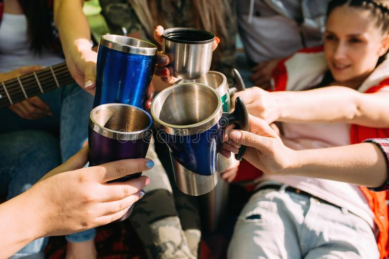 Friends group get warm with tea in the tent. Picnic time stock images